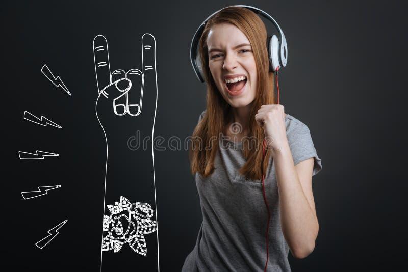 Fille énergique criant tout en écoutant la musique rock dans des ses écouteurs photographie stock