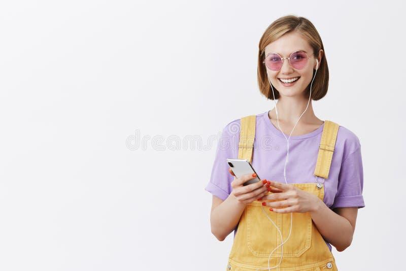 Fille étant prête pour marcher de la maison, mettant sur des écouteurs et sélectionnant la chanson positive, se tenant dans la sa image libre de droits