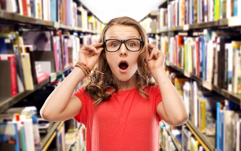 Fille étonnée d'étudiant en verres à la bibliothèque photo libre de droits