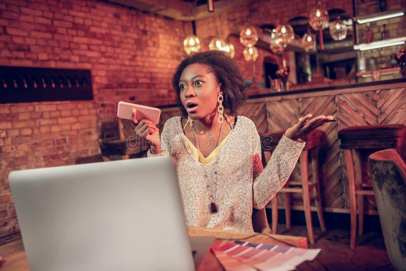Fille étonnée d'afro-américain exprimant des émotions parmi tenir le téléphone en café photos stock