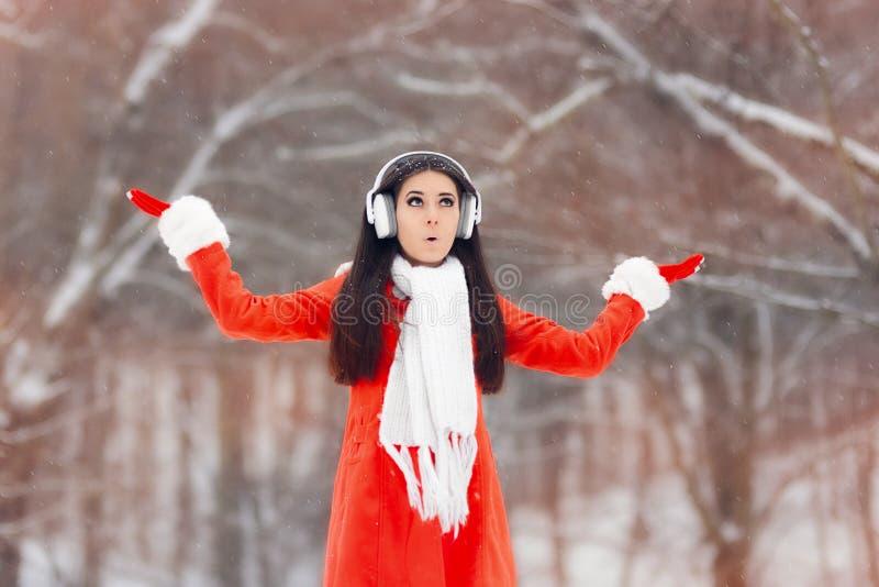 Fille étonnée d'hiver avec des écouteurs appréciant la neige photo libre de droits