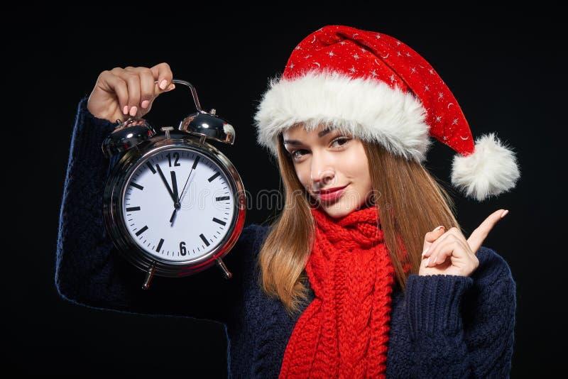 Fille étonnée dans le chapeau de Santa avec l'horloge photographie stock
