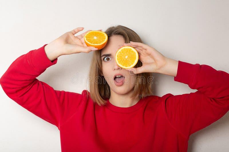 Fille étonnée de brune posant avec une demi orange, couvrant des yeux d'orange contre le mur blanc image stock