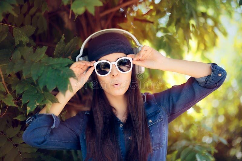 Fille étonnée de mode de denim avec des lunettes de soleil écoutant la musique sur ses écouteurs photos stock