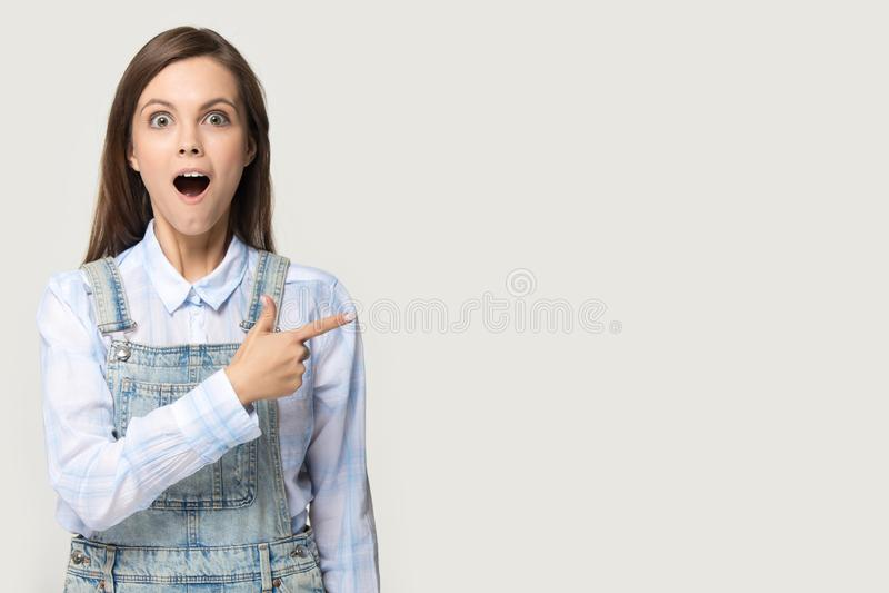 Fille étonnée dirigeant le doigt de côté au fond gris de studio de copyspace photo stock