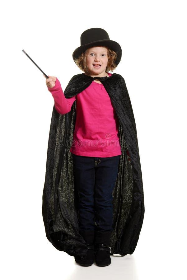 Fille étonnée habillée en tant que tache floue de mouvement de magicien sur la baguette magique images stock