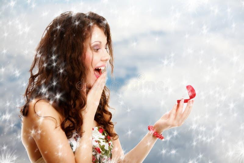 Fille étonnée ouvrant le boîte-cadeau rouge avec la bague de fiançailles. Hiver. images stock