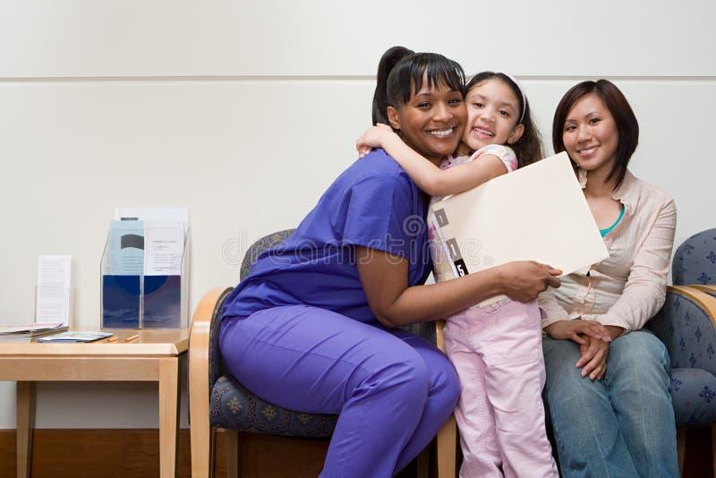 Fille étreignant l'infirmière image libre de droits