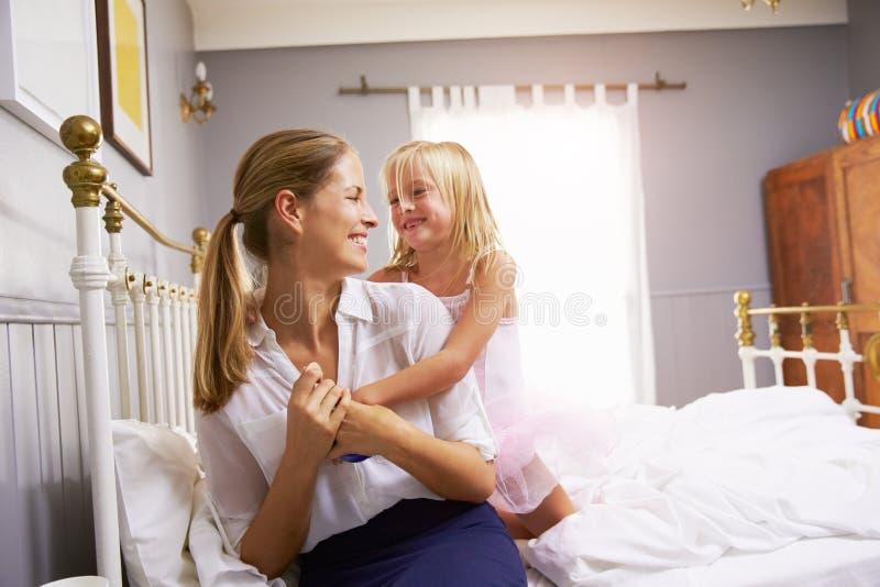Fille étreignant la mère comme elle obtient habillée pour le travail photo stock