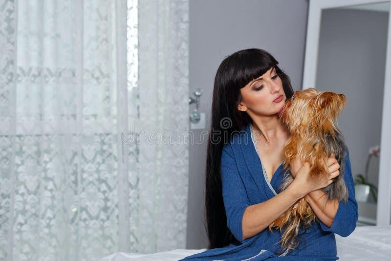 Fille étreignant Yorkshire Terrier image stock