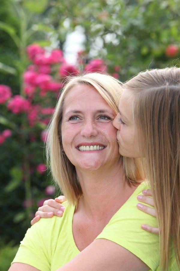 Fille adolescente affectueuse embrassant sa mère de sourire images libres de droits