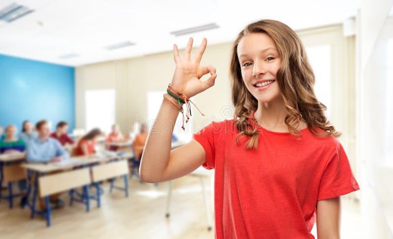 Fille adolescente de sourire d'étudiant montrant correct à l'école photo libre de droits