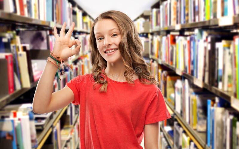 Fille adolescente de sourire d'étudiant montrant correct à la bibliothèque photo stock