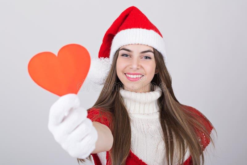Fille adolescente mignonne de Santa montrant le coeur rouge photo stock