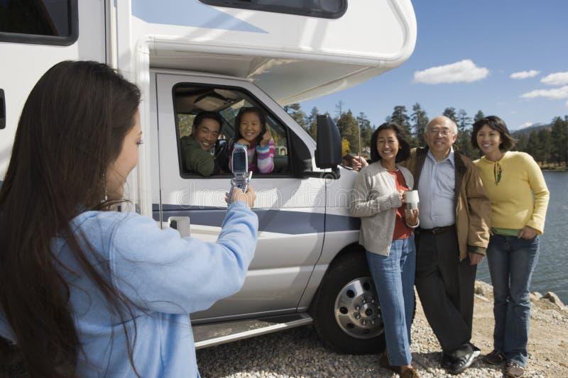 Fille adolescente photographiant la famille avec le téléphone portable en dehors du rv au lac photos libres de droits