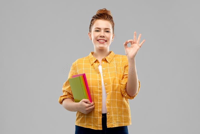 Fille adolescente rousse d'étudiant avec la représentation de livres correcte photo stock