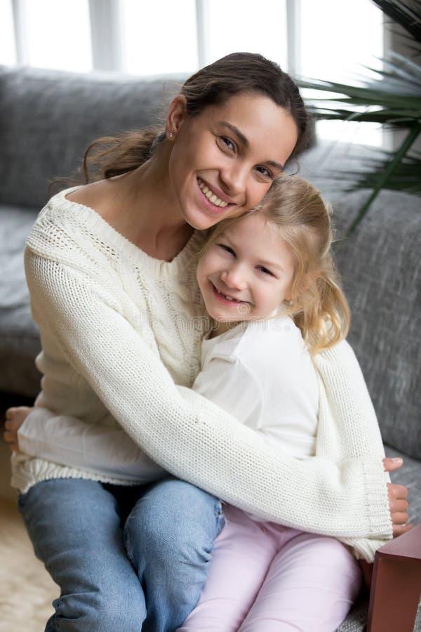Fille adoptée de embrassement de mère heureuse regardant l'appareil-photo, vertical photographie stock libre de droits