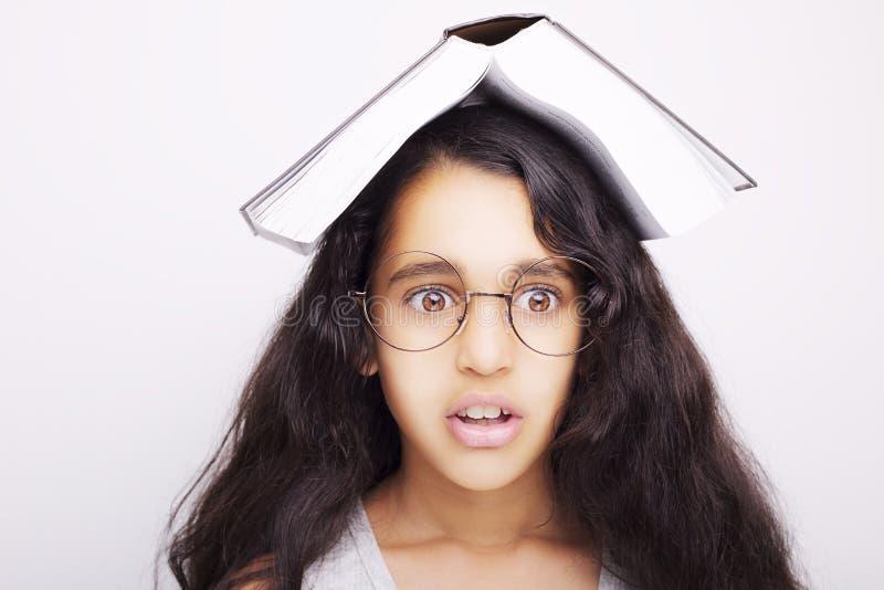 Fille adorable étudiant avec les lunettes et le livre sur la tête image libre de droits