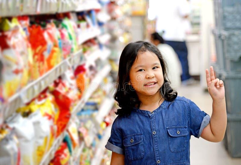 Fille adorable aux étagères dans le supermarché photos stock