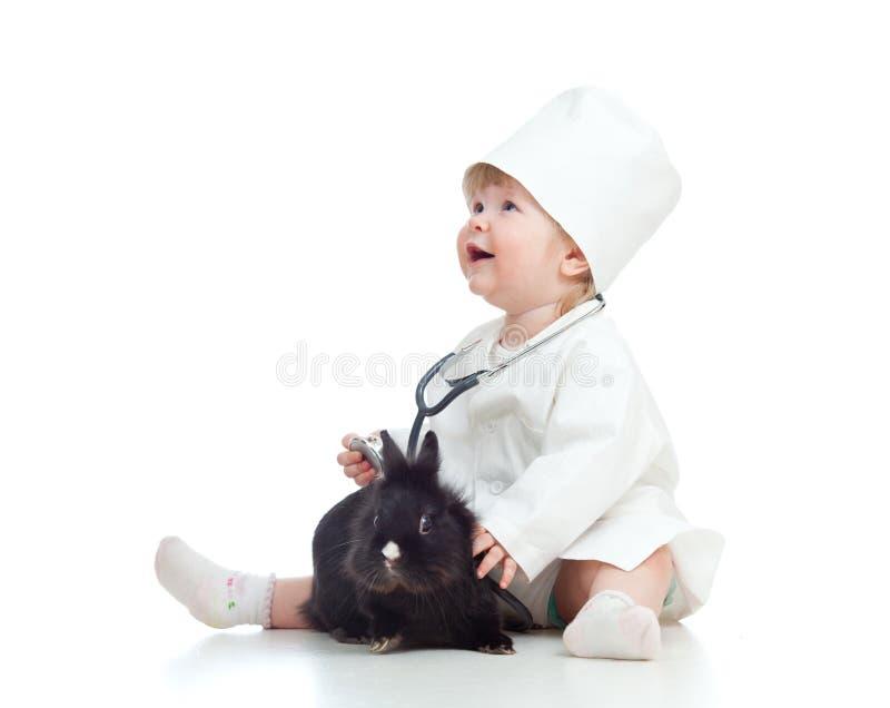 Fille adorable avec des vêtements de docteur et de lapin images libres de droits