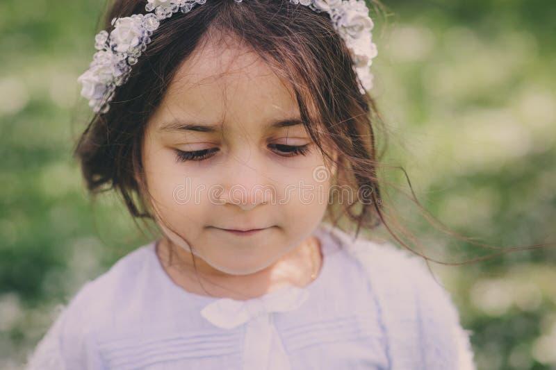 Fille adorable d'enfant d'enfant en bas âge dans l'équipement élégant bleu-clair marchant et jouant dans le jardin de floraison d photo libre de droits