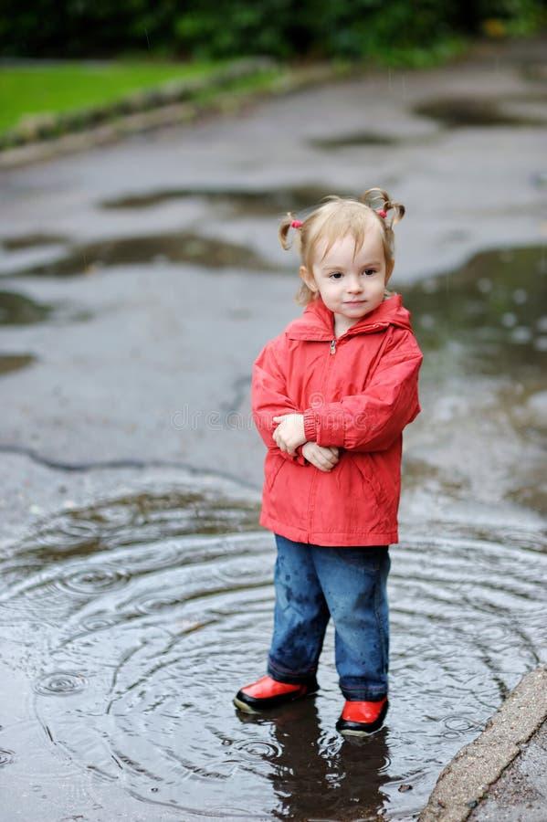 Fille adorable d'enfant en bas âge au jour pluvieux images stock