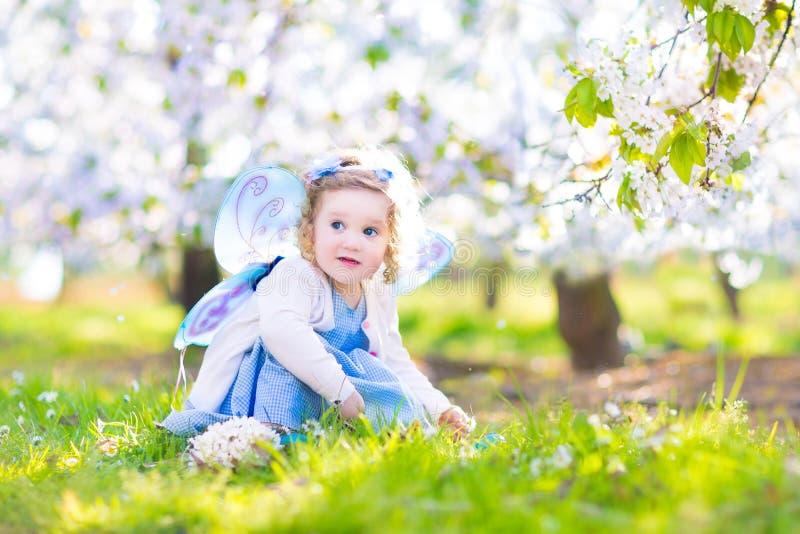 Fille adorable d'enfant en bas âge dans le costume féerique dans le jardin de fruit image libre de droits