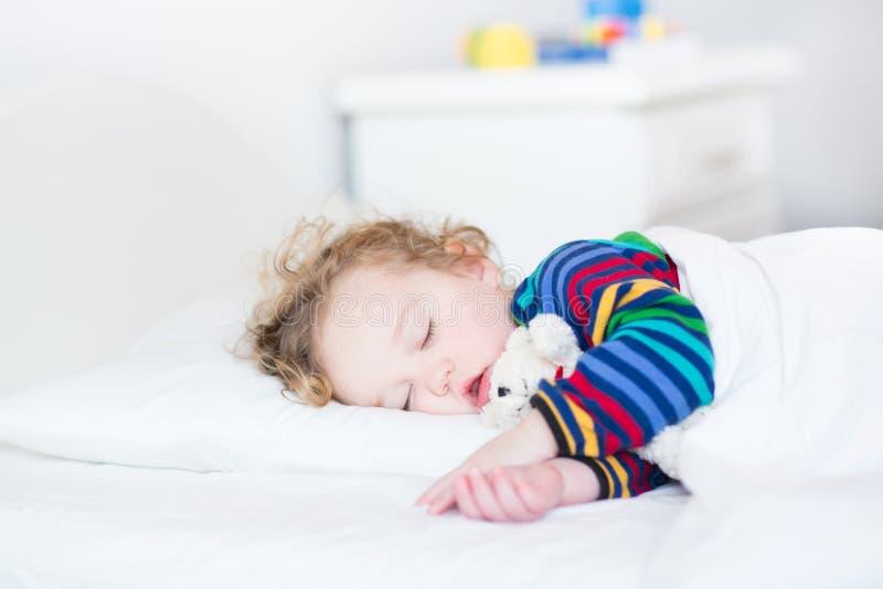Fille adorable d'enfant en bas âge prenant un petit somme dans un lit blanc image libre de droits
