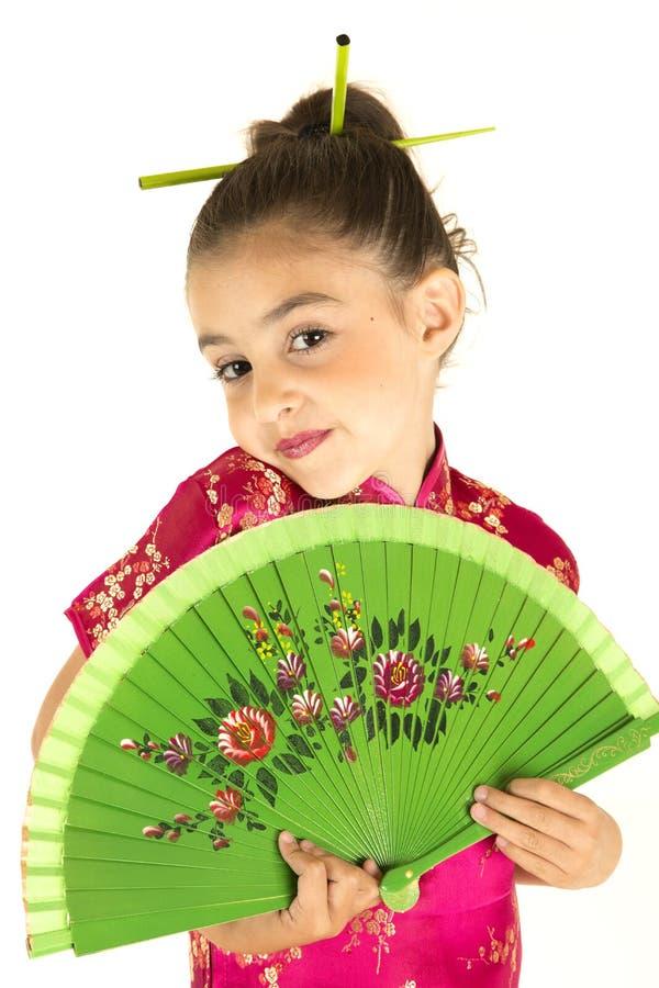 Fille adorable dans la robe asiatique montrant une expression effarouchée image libre de droits