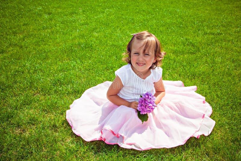 Fille adorable dans une jupe rose avec la fleur dans le jardin images stock