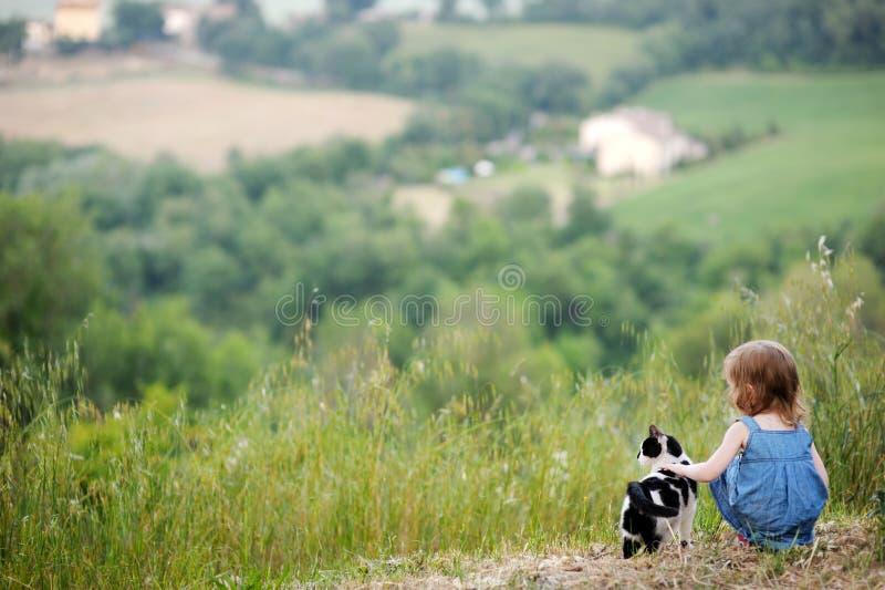 Fille adorable et un chat à l'extérieur image stock