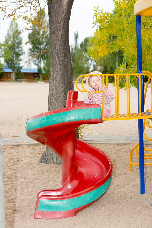 Fille adorable heureuse d'enfant sur l'oscillation sur le terrain de jeu près du jardin d'enfants Montessori le jour d'été photos stock