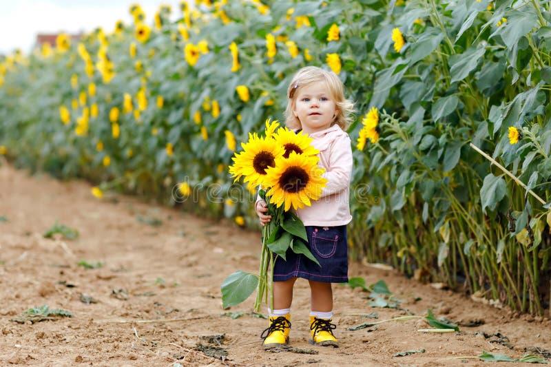 Fille adorable mignonne d'enfant en bas âge sur le gisement de tournesol avec les fleurs jaunes Bel enfant de bébé avec les poils photos stock