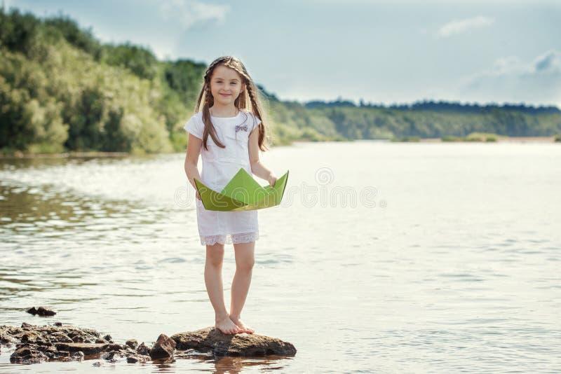 Fille adorable posant avec le bateau de papier sur le lac image stock