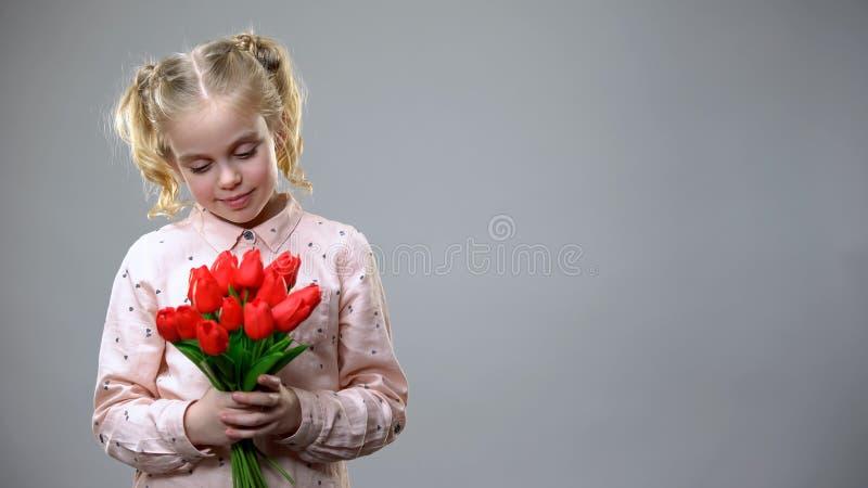 Fille adorable regardant sur les fleurs rouges dans des mains, fond gris, humeur de vacances photographie stock