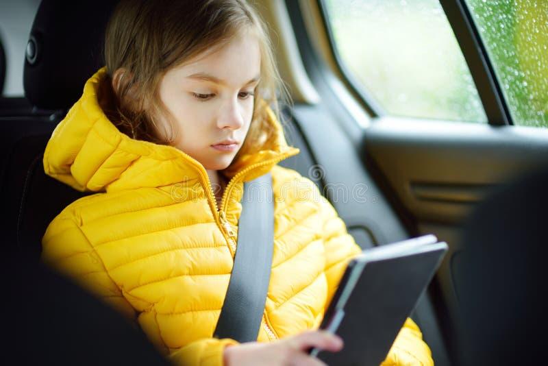 Fille adorable s'asseyant dans une voiture et lisant son ebook le jour pluvieux d'automne Herserf amusant d'enfant sur un voyage  image libre de droits