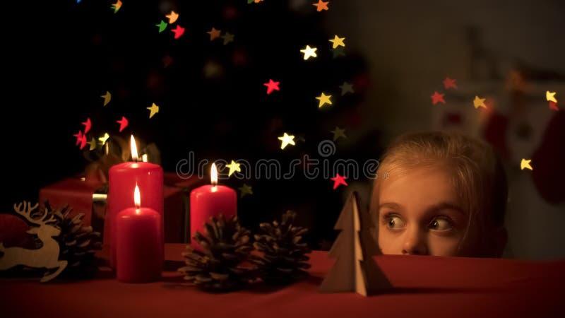 Fille adorable semblant secrètement les jouets en bois, scintillement d'arbre de Noël, enfance image libre de droits