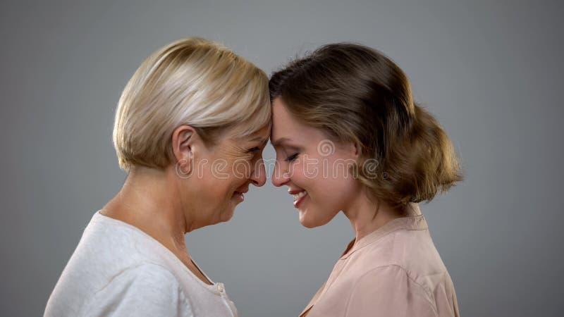 Fille adulte et m?re touchant des fronts se regardant, amour de famille image libre de droits