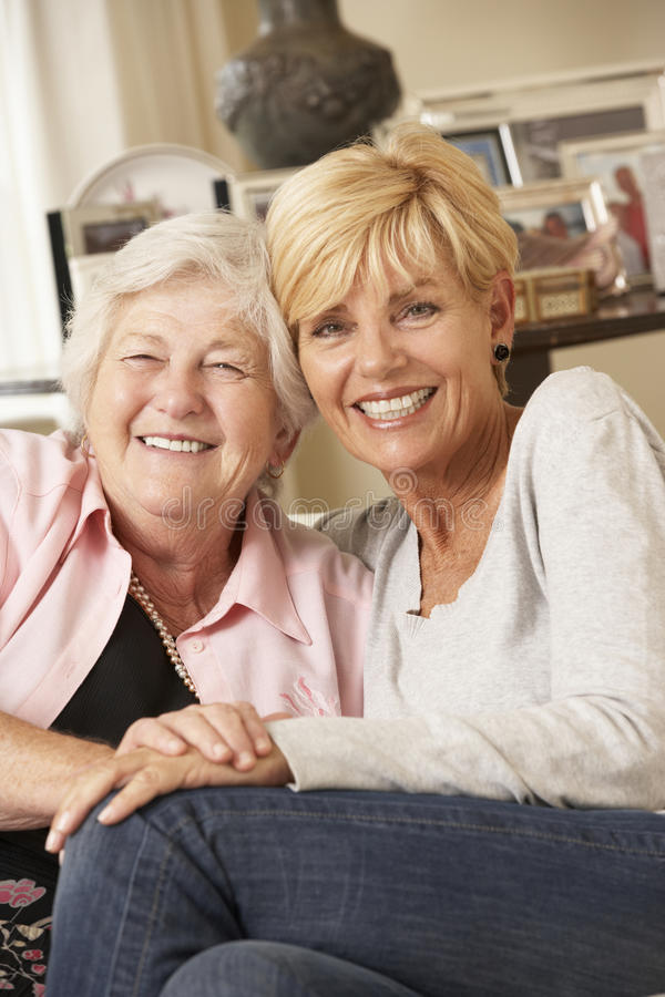 Fille adulte rendant visite à la mère supérieure s'asseyant sur Sofa At Home photographie stock libre de droits