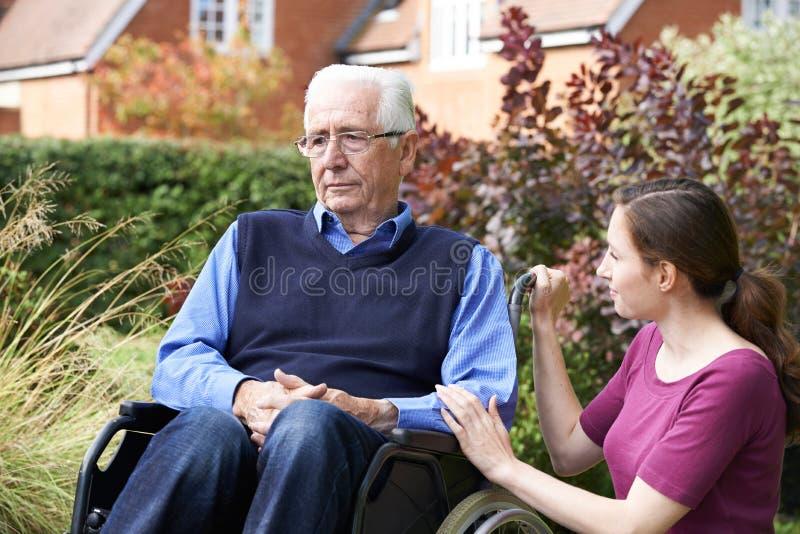 Fille adulte soulageant le père supérieur In Wheelchair images stock