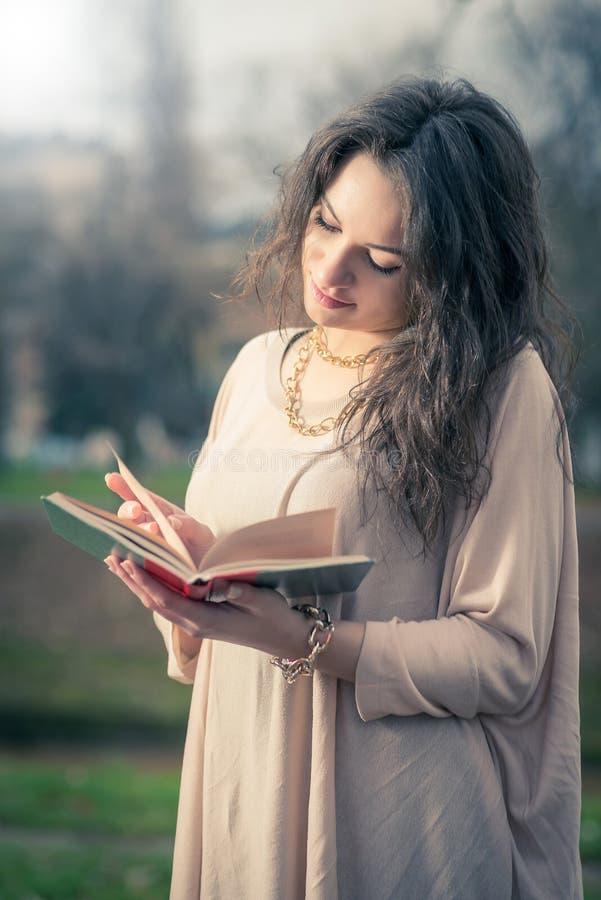 Fille affichant un livre en stationnement photographie stock