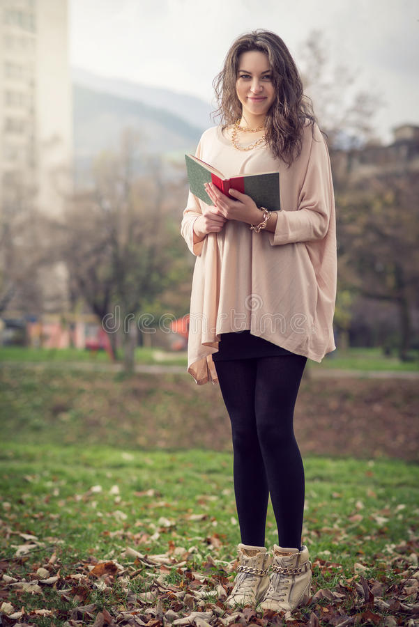 Fille affichant un livre en stationnement photo stock