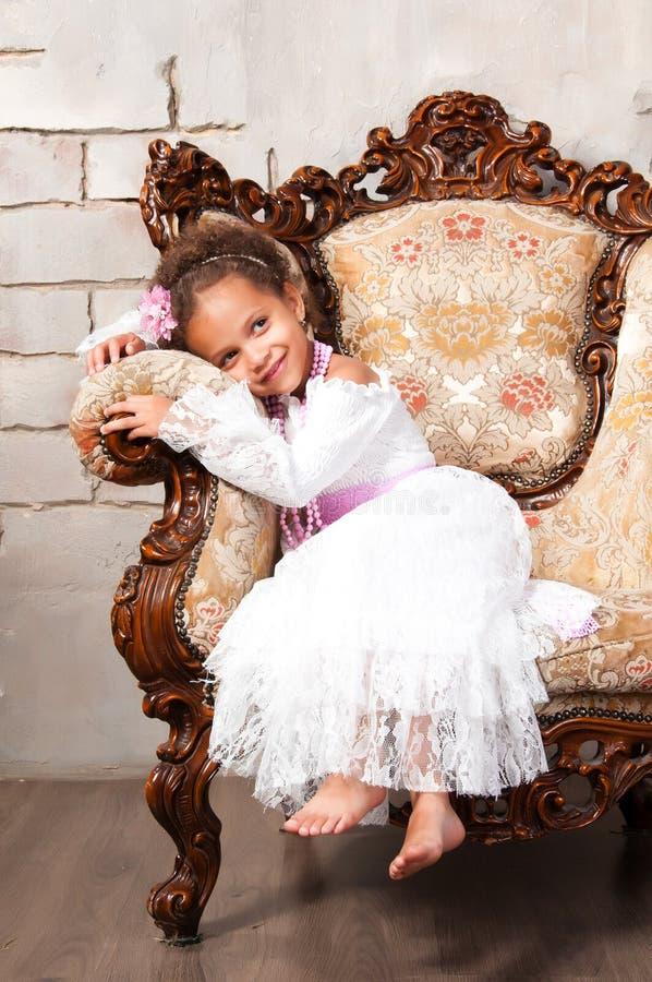 Fille africaine de sourire de portrait en gros plan dans une robe blanche de dentelle sur la chaise de vintage images stock