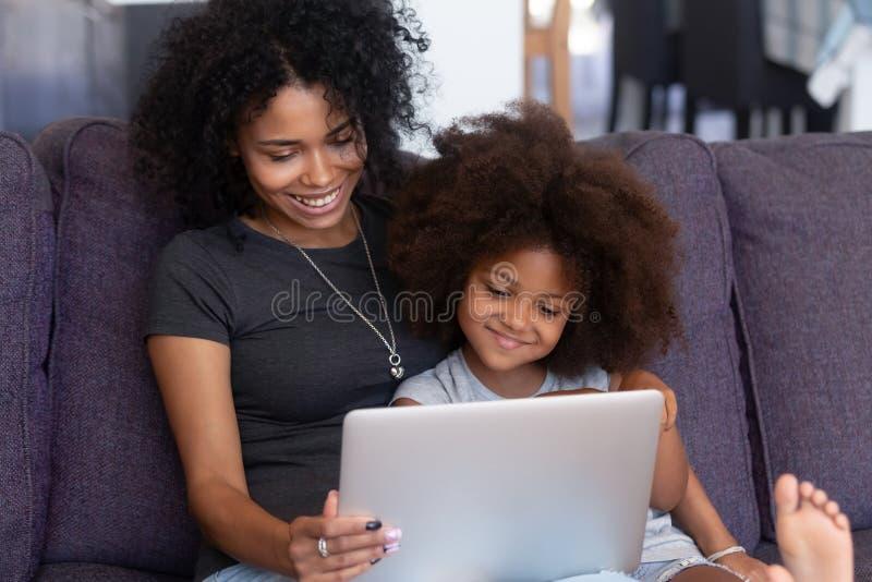 Fille africaine de sourire de mère et d'enfant ayant l'amusement avec l'ordinateur photos stock