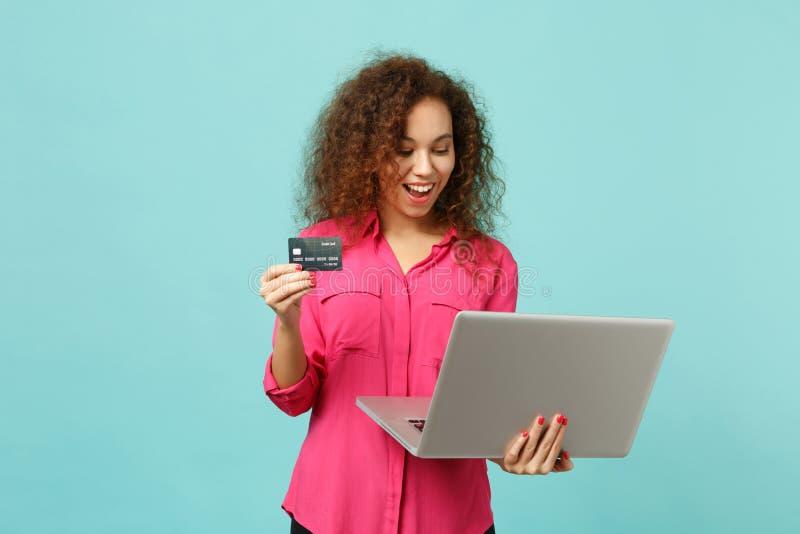 Fille africaine drôle dans des vêtements sport utilisant l'ordinateur de PC d'ordinateur portable, jugeant la carte de banque de  image libre de droits