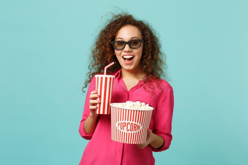 Fille africaine excitée en verres de l'imax 3d observant la tasse de maïs éclaté de prise de pellicule cinématographique de soude images libres de droits