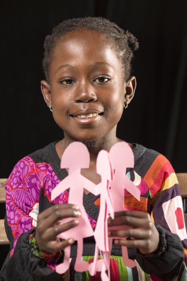 Fille africaine jouant avec les poupées de papier photo stock