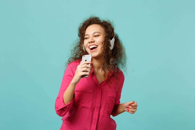 Fille africaine joyeuse dans le téléphone portable de prise de vêtements sport, musique de écoute avec des écouteurs d'isolement  photographie stock