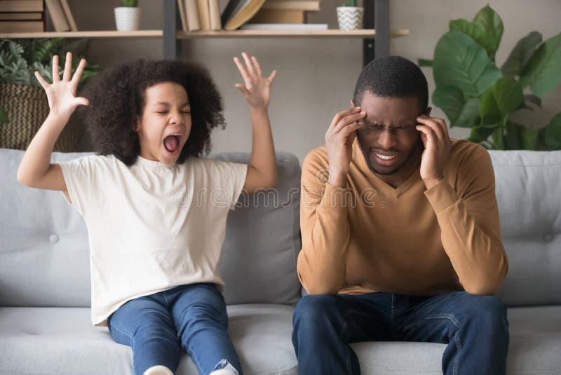 Fille africaine têtue d'enfant dans l'mauvaise humeur criant au père noir images stock