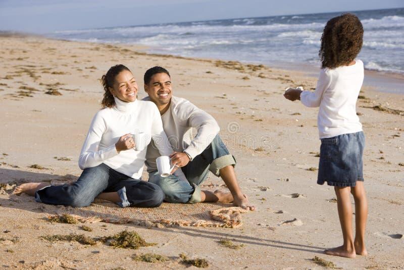 Fille afro-américaine avec des parents sur la plage photos libres de droits